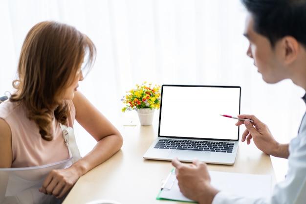 Lekarz specjalista wyjaśnia i pokazuje pacjentowi wyniki na komputerze przenośnym