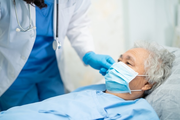 Lekarz sprawdza azjatycką starszą pacjentkę noszącą maskę na twarz w celu ochrony wirusa coronavirus covid-19.