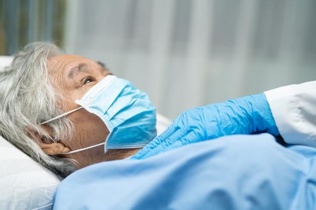 Lekarz sprawdza azjatycką starszą pacjentkę noszącą maskę na twarzy w szpitalu w celu ochrony koronawirusa covid-19.