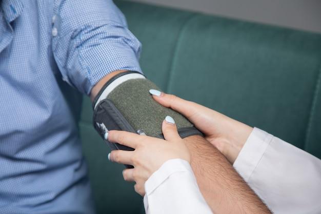 Lekarz sprawdza ciśnienie krwi mężczyzny za pomocą urządzenia elektronicznego na kanapie