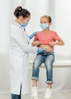 Lekarz sprawdza dziewczynę z maską