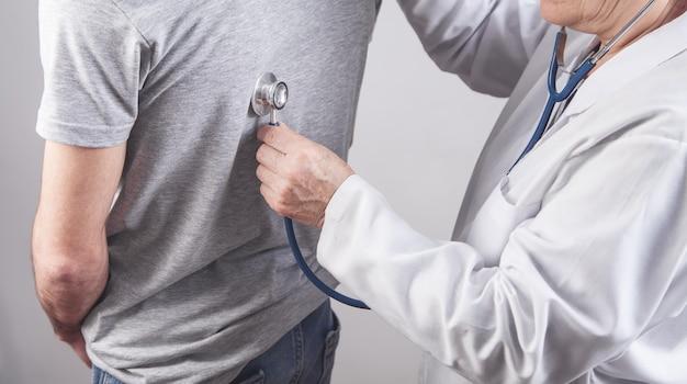 Lekarz sprawdza pacjenta z powrotem stetoskopem w szpitalu.