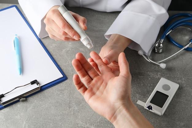 Lekarz sprawdza poziom cukru we krwi u pacjenta z cukrzycą na szarym stole