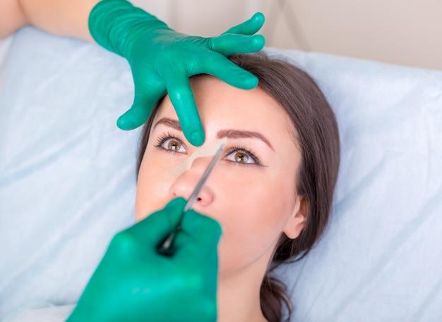 Lekarz sprawdza twarz kobiety, powiekę przed operacją plastyczną, plastykę powiek.