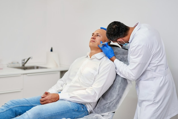 Lekarz sprawdza ucho człowieka z otoskopem