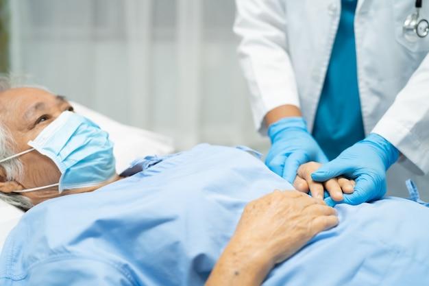 Lekarz sprawdzający pacjenta azjatyckiej starszej kobiety w masce na twarz w celu ochrony wirusa covid-19