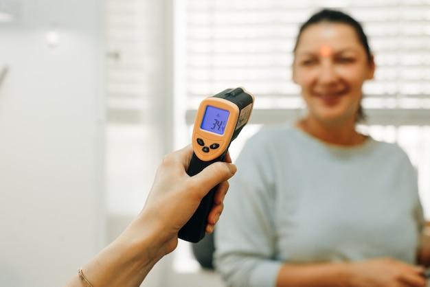 Lekarz sprawdzający temperaturę kobiety za pomocą procesu sprawdzania termometru cenzorowego