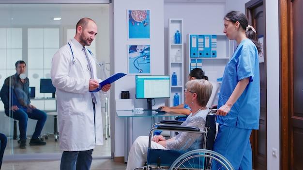 Lekarz sprawdzanie diagnozy niepełnosprawnej starszej kobiety na wózku inwalidzkim. personel medyczny na korytarzu szpitala z pacjentem z inwalidztwem. mężczyzna w pokoju badań lekarskich.
