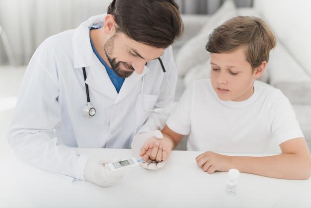 Lekarz sprawdzi krew dziecka pod kątem poziomu cukru.