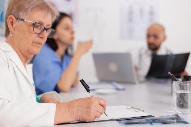 Lekarz starszy kobieta w białym fartuchu analizujący badanie lekarskie przepisujący lek na pigułki piszący leczenie choroby w schowku on