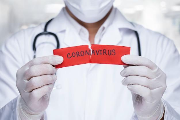 Lekarz stetoskopem darcie czerwonego papieru słowem koronawirus.