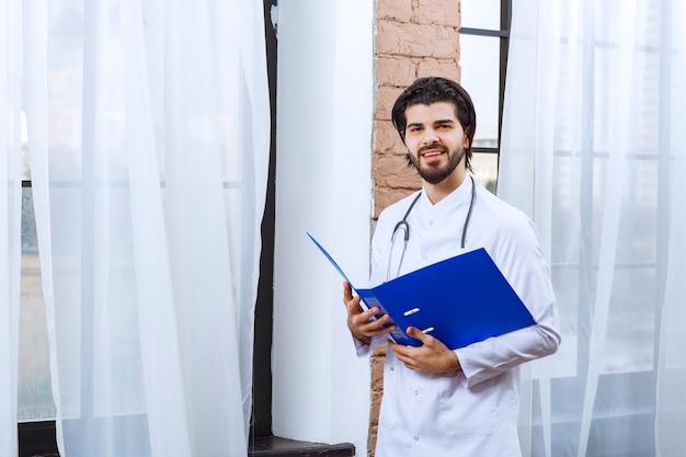 Lekarz stetoskopem posiadający niebieski folder sprawozdawczy.
