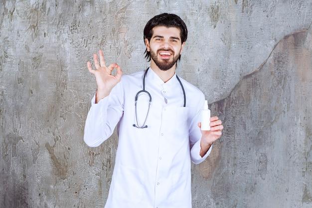 Lekarz stetoskopem trzymający białą tubkę sprayu do dezynfekcji rąk i cieszący się produktem.