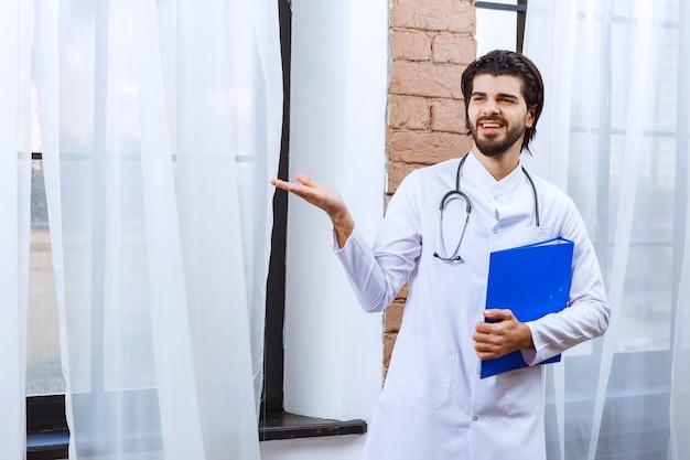 Lekarz stetoskopem trzymający niebieski folder sprawozdawczy i wskazujący na kogoś w pobliżu.