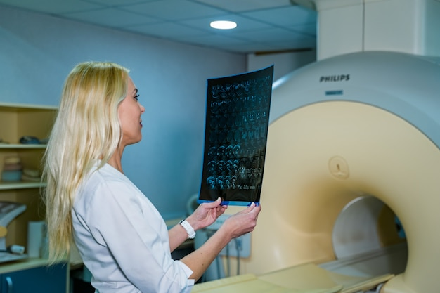 Lekarz stojący w biurze z x ray w tle. medyczny portret mężczyzny. pojęcie medyczne. zdjęcie poziome.