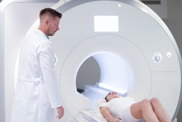 Lekarz stojący w pobliżu pacjenta leżącego w maszynie mri w klinice. nowoczesne metody badania koncepcji pacjentów onkologicznych