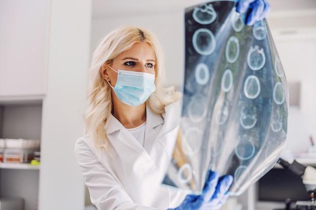 Lekarz stojący w szpitalu i patrząc na prześwietlenie mózgu pacjenta.