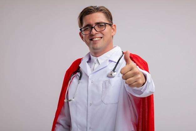 Lekarz superbohatera mężczyzna ubrany w biały płaszcz w czerwonej pelerynie i okularach ze stetoskopem na szyi z uśmiechem na twarzy pokazujący kciuki do góry stojąc nad białą ścianą