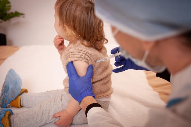 Lekarz szczepi dziecko przeciwko koronawirusowi. dziecko płacze i boi się. mężczyzna w szlafroku, czapce, masce i rękawiczkach robi zastrzyk dziecku. kwarantanna domowa, covid.