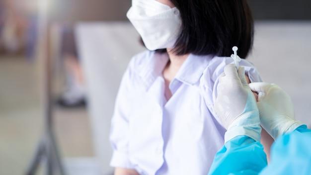 Lekarz szczepi uczniów w mundurach, aby zapobiec koronawirusowi lub covid-19