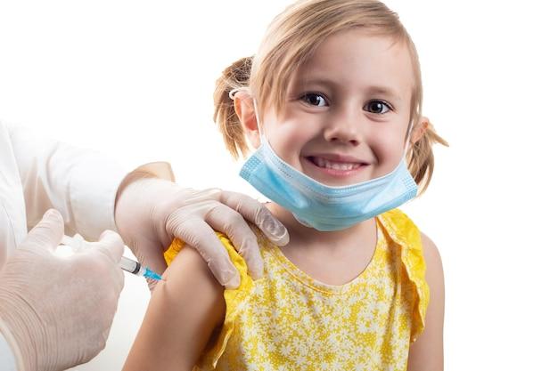 Lekarz szczepiący śliczną uśmiechniętą małą dziewczynkę na sobie żółtą sukienkę i maskę ochronną na twarz