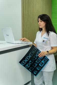 Lekarz szpitalny trzymający kliszę rentgenowską pacjenta. nowoczesne biuro tło. koncepcja opieki zdrowotnej, rentgen, ludzie i medycyna.