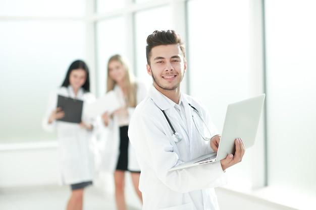 Lekarz terapeuta korzysta z laptopa stojąc na korytarzu gabinetu
