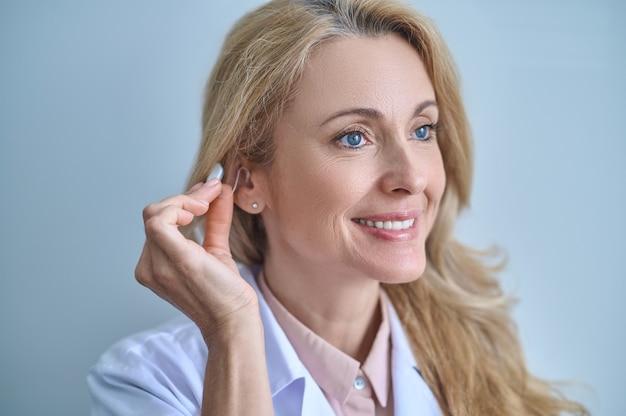 Lekarz testujący aparat słuchowy w uchu