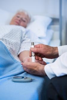 Lekarz testujący cukrzycę starszego pacjenta za pomocą wstrzykiwacza insuliny