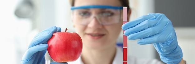 Lekarz trzyma czerwone jabłko i pasek z pomiarami określającymi dojrzałość owoców
