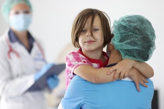 Lekarz trzyma dziewczynę w ramionach w gabinecie lekarskim