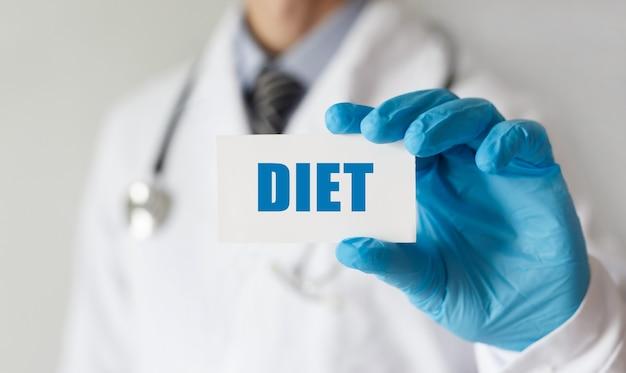 Lekarz trzyma kartę z tekstem dieta, pojęcie medyczne