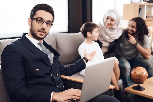 Lekarz trzyma laptopa i wskazuje na rodzinę.