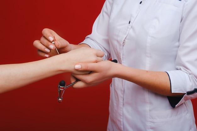 Lekarz trzyma młotek neurologiczny na czerwonym tle. neurolog przy pomocy młotka sprawdza odruchy pacjenta. diagnostyka, opieka zdrowotna i opieka medyczna