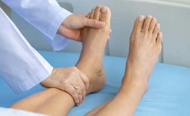 Lekarz trzyma nogi pacjenta na łóżku w szpitalu i sprawdzanie układu nerwowego w celu wyleczenia i leczenia. pojęcie zespołu guillain-barre i choroby zdrętwiałych rąk lub efekt uboczny szczepionki.