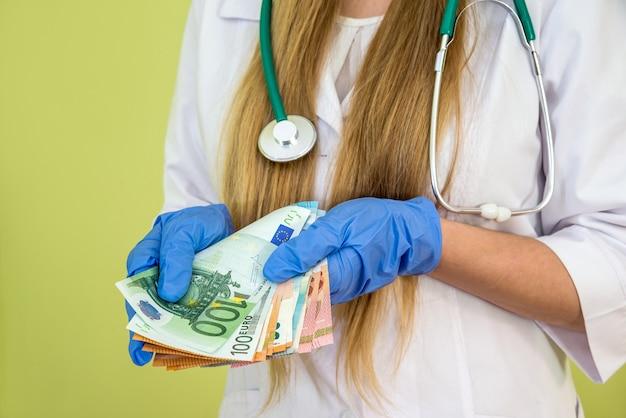 Lekarz trzyma pieniądze euro na zielono