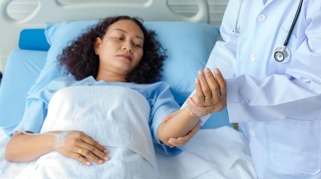 Lekarz trzyma rękę azjatyckiej pacjentki na łóżku w szpitalu i sprawdzanie układu nerwowego w celu wyleczenia i leczenia. pojęcie zespołu guillain-barre i choroby zdrętwiałych rąk lub efekt uboczny szczepionki.