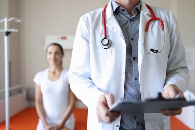 Lekarz trzyma schowek z dokumentami medycznymi w tle pacjent siedzi medyczny