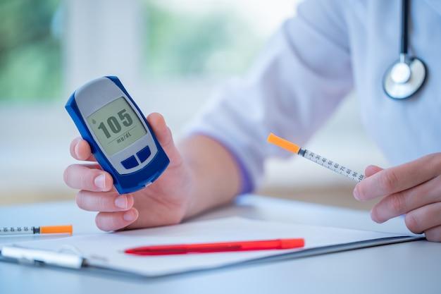 Lekarz trzyma strzykawkę do wstrzykiwania insuliny i pokazuje pacjentowi z cukrzycą glukometr z poziomem glukozy we krwi podczas konsultacji lekarskiej i badania w szpitalu. cukrzycowy styl życia i opieka zdrowotna