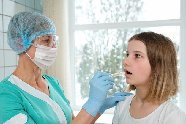 Lekarz trzyma termometr w ustach młodej dziewczyny do pomiaru temperatury.