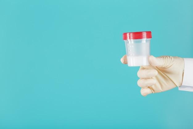 Lekarz trzyma w dłoni plastikowy słoik z nasieniem do analizy. uczęszczający do lekarza rodzinnego w białym fartuchu i gumowych rękawiczkach na cyjanowym tle. wolna przestrzeń.