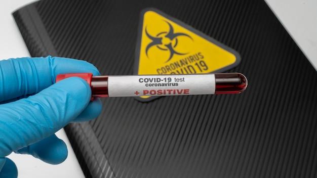 Lekarz trzyma w dłoni szczepionkę koronawirusa covid 19, zainfekowaną próbkę krwi w probówce, szczepionkę i zastrzyk ze strzykawki. jest stosowany do zapobiegania, immunizacji i leczenia z użyciem covid-19
