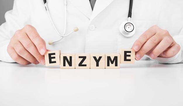 Lekarz trzyma w rękach drewniane kostki z napisem enzyme