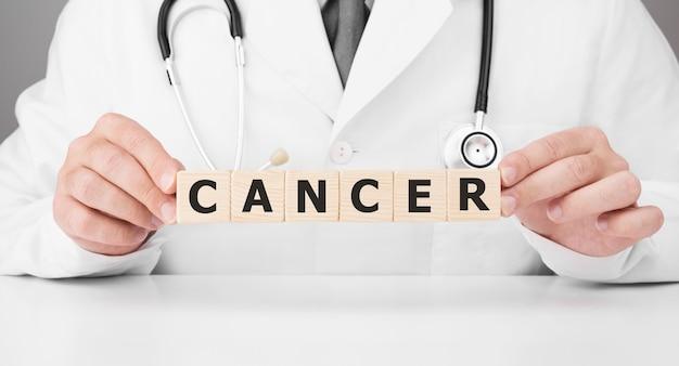 Lekarz trzyma w rękach drewniane kostki z napisem rak