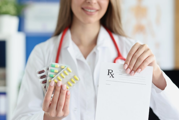 Lekarz trzyma w ręku słoik tabletek i formularz recepty
