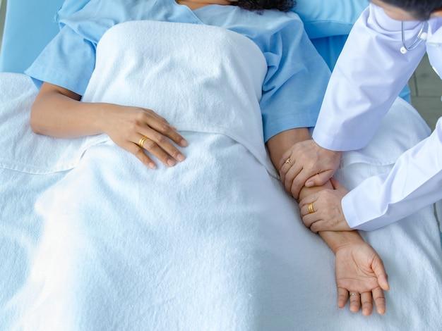 Lekarz trzymać rękę pacjenta na łóżku w szpitalu i sprawdzanie układu nerwowego w celu wyleczenia i leczenia. pojęcie zespołu guillain-barre i choroby zdrętwiałych rąk lub efekt uboczny szczepionki.