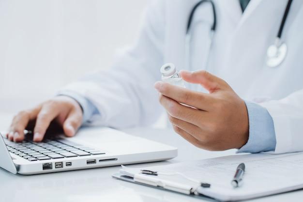 Lekarz trzymając butelkę recepty z laptopa wpisując receptę na specjalnym formularzu w sali biurowej. koncepcja opieki zdrowotnej, szczepionki, medycyny i farmacji.