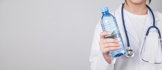 Lekarz trzymając butelkę wody.