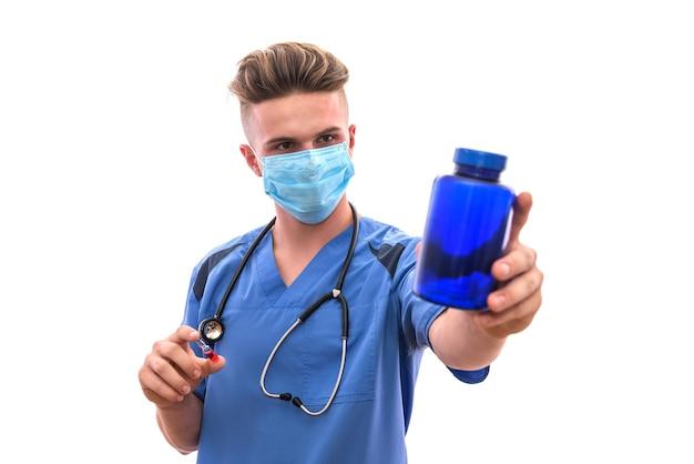 Lekarz trzymając butelkę z pigułkami na białym tle na białej ścianie