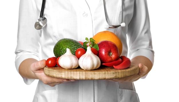 Lekarz trzymając deskę z sercem zdrowej żywności na białym tle
